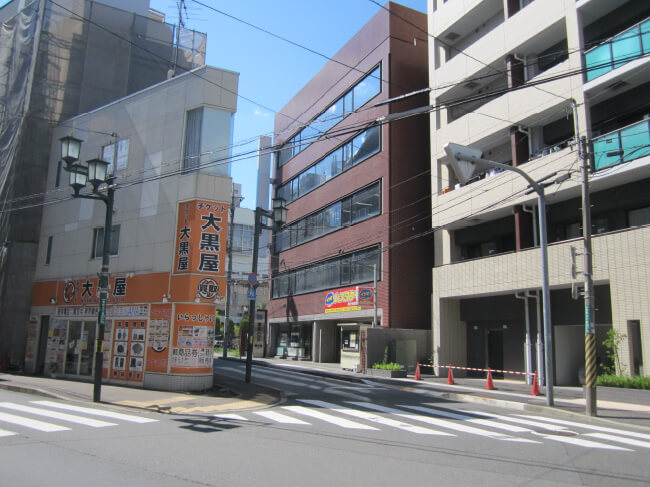藤和ハウスとチケット大黒屋のある交差点を右手前方向に進むと、右側の茶色のビルの4階が事務所です。